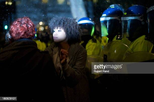 Young woman is surrounded by riot police during a student protest in London against the rise in university tuition fees.