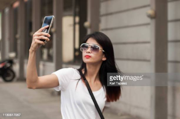 A young woman is taking a selfie in the city sidewalk