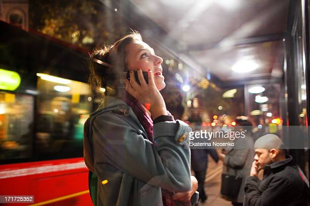 Young woman is talking on her mobile phone at a bus stop on a busy evening Oxford street in London.