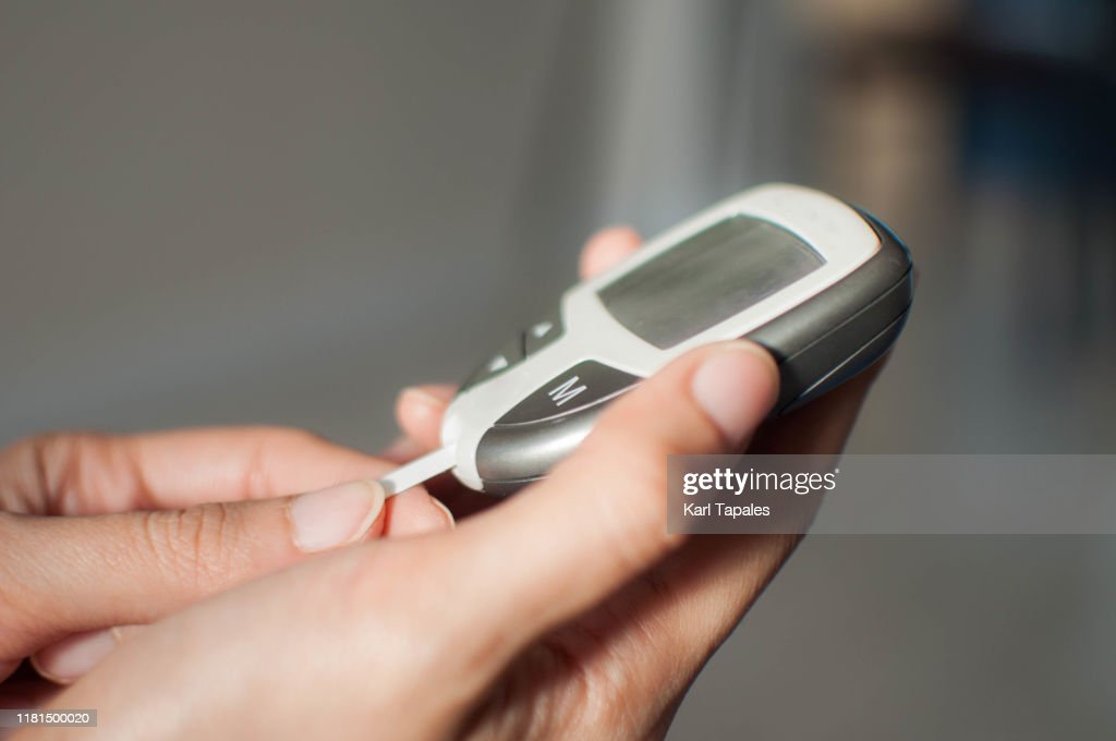 A young woman is using a glucometer : Stockfoto