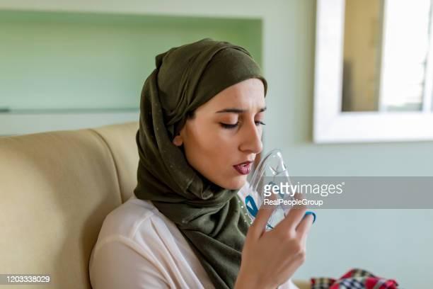 young woman is using an asthma inhaler - amigdalite imagens e fotografias de stock