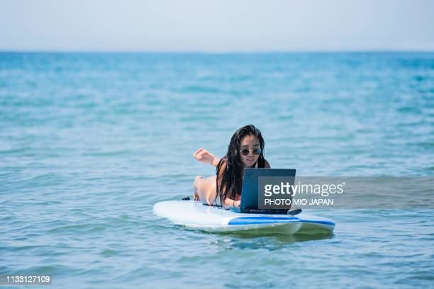 a young woman  is using  laptop on a surfboard - フリーランス ストックフォトと画像