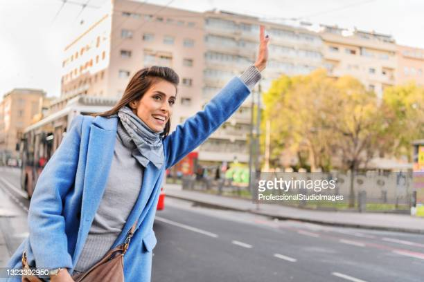 a young woman is waving to catch a cab in the city street. - world sports championship stock pictures, royalty-free photos & images