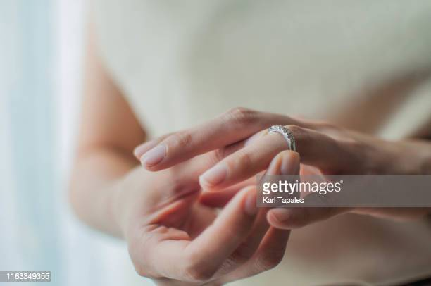 a young woman is wearing her wedding ring - wedding ring stock pictures, royalty-free photos & images