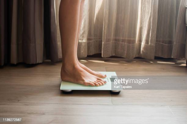 a young woman is weighing herself in a weighing scale - scale stock pictures, royalty-free photos & images