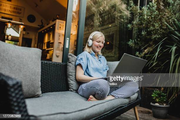a young woman is working from home on the balcony - makeshift stock pictures, royalty-free photos & images