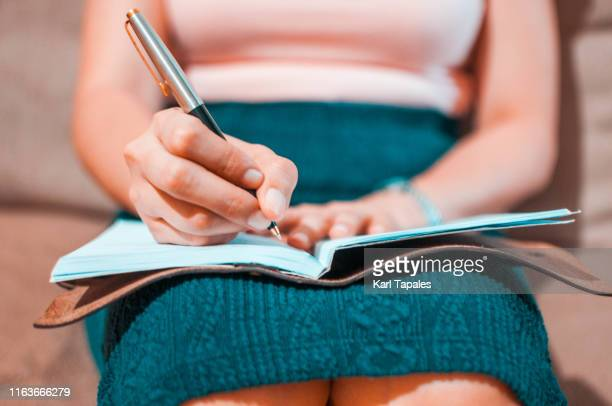 a young woman is writing on her journal while sitting on a couch - list stock pictures, royalty-free photos & images