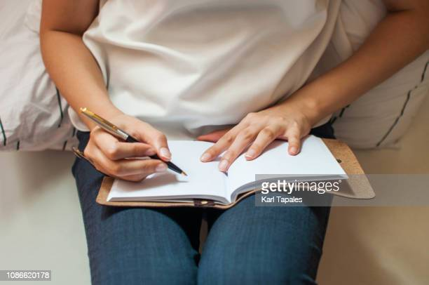 a young woman is writing on her personal organizer - diary stock pictures, royalty-free photos & images