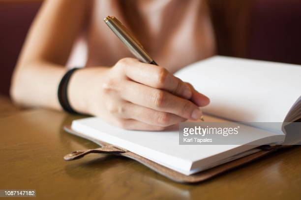 a young woman is writing on her personal organizer - authors photos et images de collection