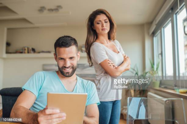 young woman jealously looking at the smiling man using digital tablet - boyfriend stock pictures, royalty-free photos & images