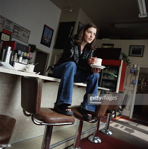 young woman jeans and leather jacket sits on a counter drinking coffee with a pensive look her face