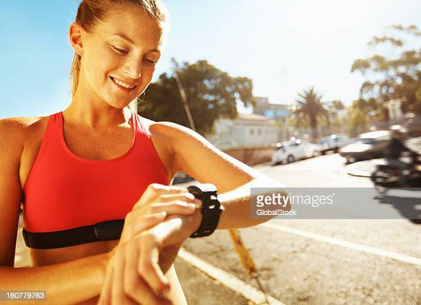 Young woman jogger looking at her running watch