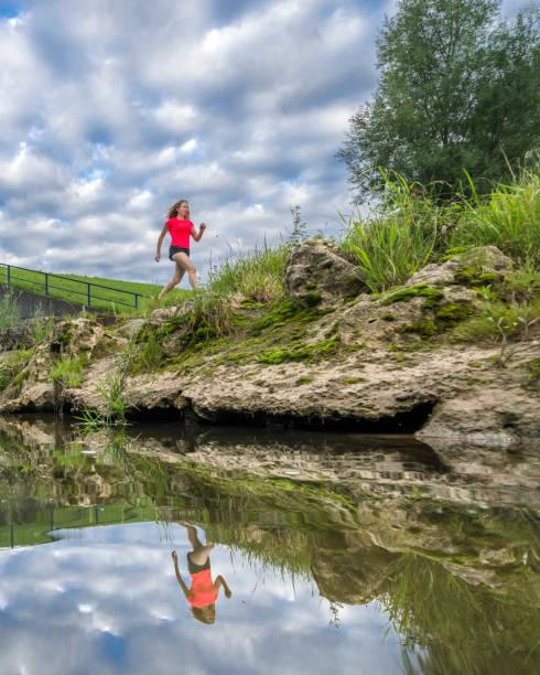 Young woman jogging along bank of Rems river