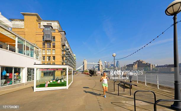 young woman jogging along pathway by the design museum and tower bridge, london - デザイン博物館 ストックフォトと画像
