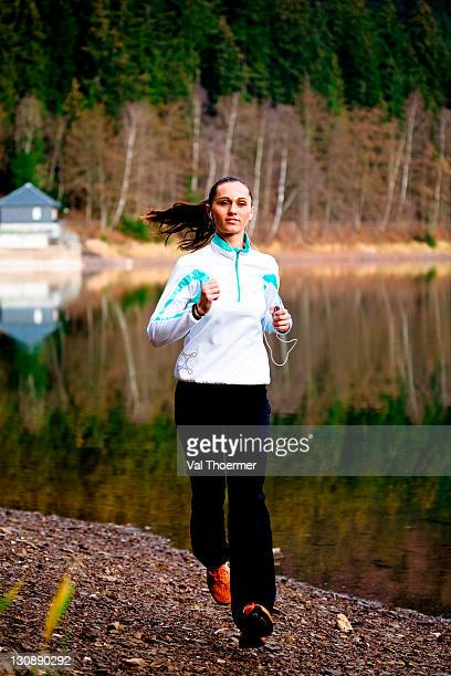 Young woman jogging at a forest lake