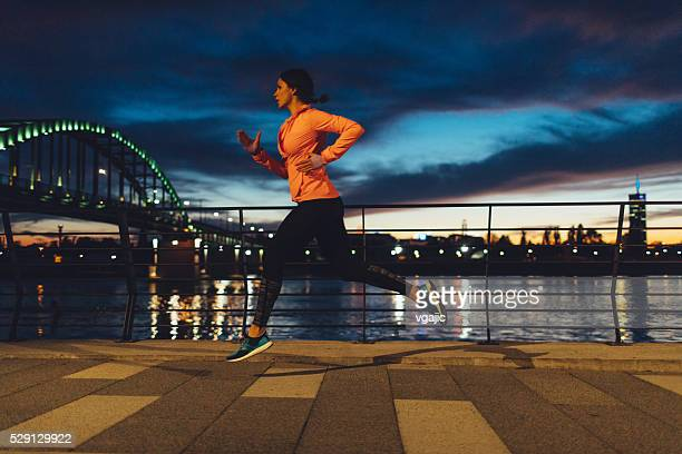 Young Woman Jogging At Night Near River.