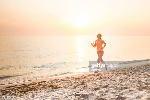 Young woman jogging at the sandy beach