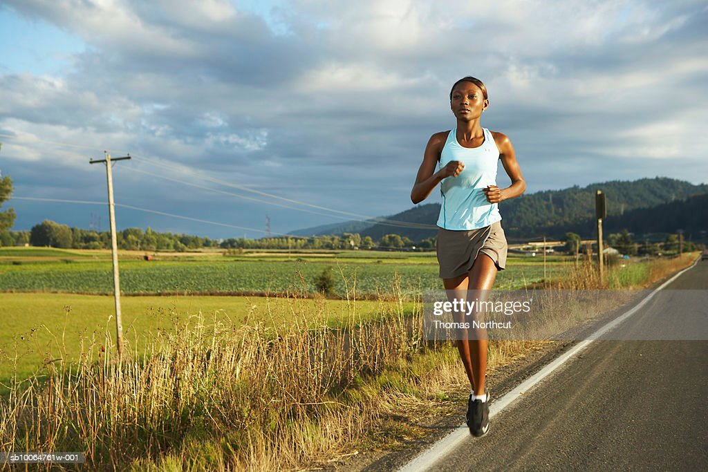Young woman jogging by road in rural landscape : Stock Photo