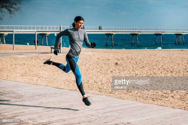 Young woman jogging by the beach