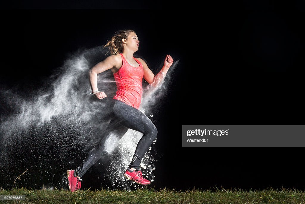 Young woman jogging in a dust cloud in front of black background : ストックフォト