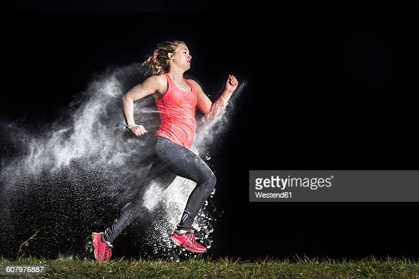 Young woman jogging in a dust cloud in front of black background