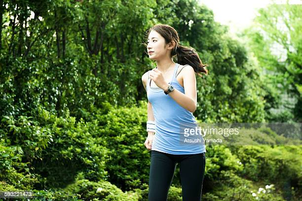 young woman jogging in park - 走る ストックフォトと画像
