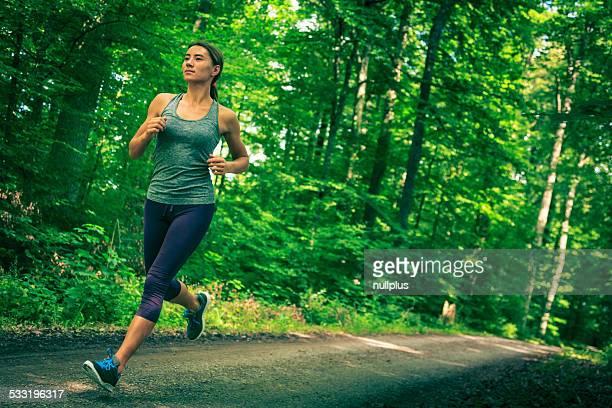Jeune femme jogging dans la forêt.