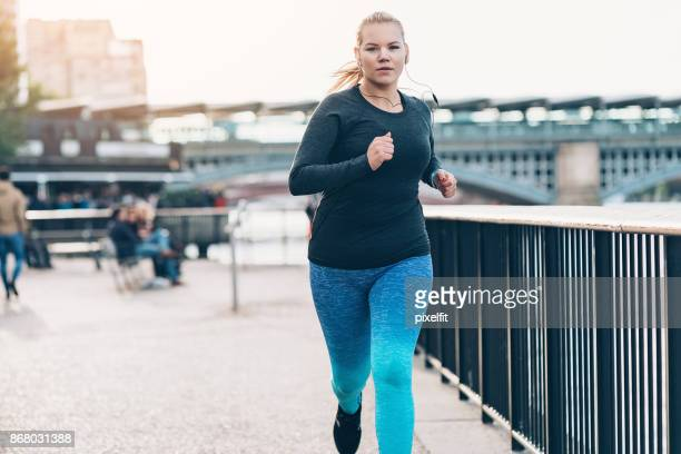 young woman jogging in the morning - curvy women stock pictures, royalty-free photos & images