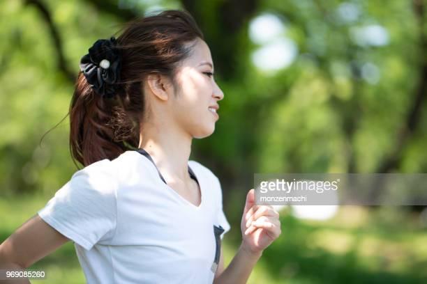 jeune femme jogging dans le parc de verdure - cadrage à la taille photos et images de collection