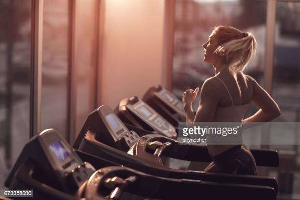 young woman jogging on a treadmill in a gym. - one young woman only stock pictures, royalty-free photos & images