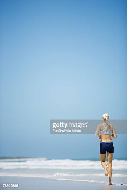 Young woman jogging on beach, rear view, full length