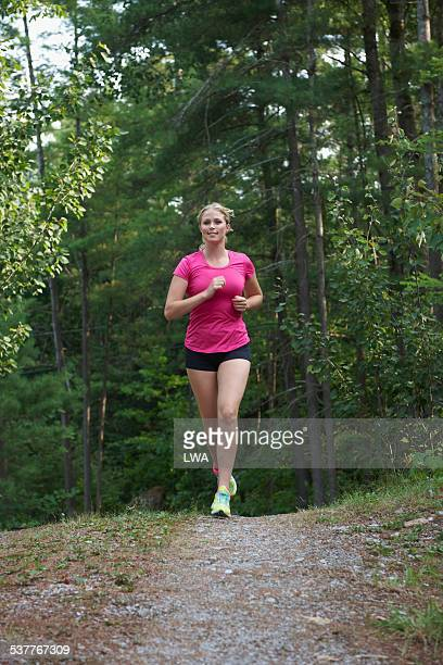 Young woman jogging on forest trail