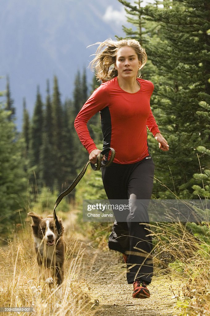 Young woman jogging on mountain path with dog : Stock Photo