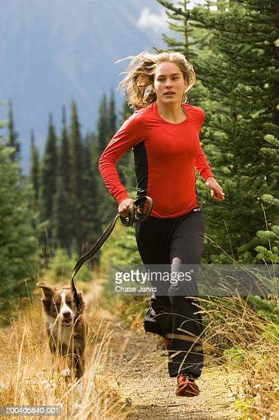 Young woman jogging on mountain path with dog