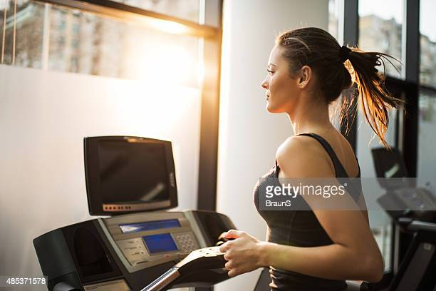 Young woman jogging on treadmill in a gym.