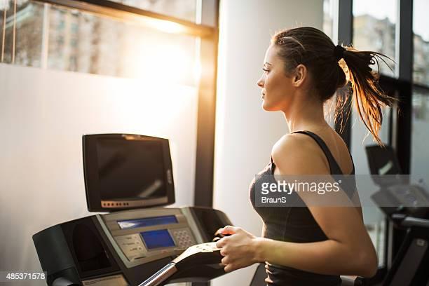 トレッドミルでのジョギングの若い女性のジムを備えています。