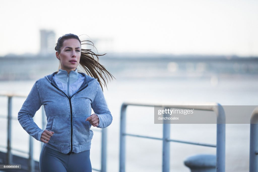 Young woman jogging outdoors close up shot : Stock Photo