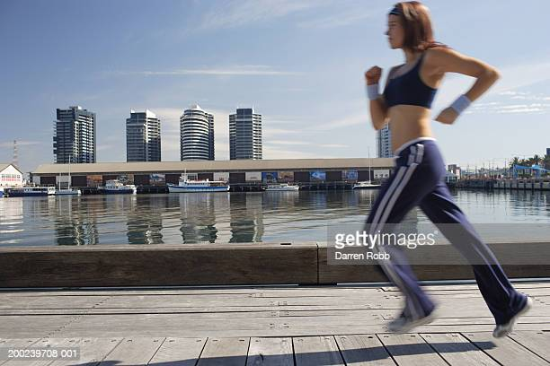 Young woman jogging outdoors, side view (blurred motion)