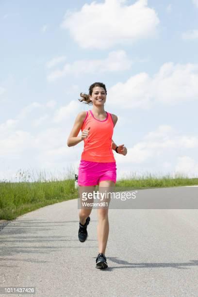young woman jogging - sportkleidung stock-fotos und bilder