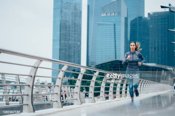 young woman jogging - center athlete stock pictures, royalty-free photos & images