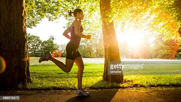 young woman jogging - public park stock photos and pictures