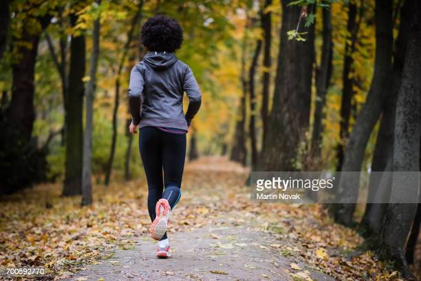 young woman jogging through the fall park, rear shot. - fall back stock photos and pictures