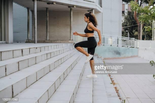 young woman jogging up steps - beha stockfoto's en -beelden