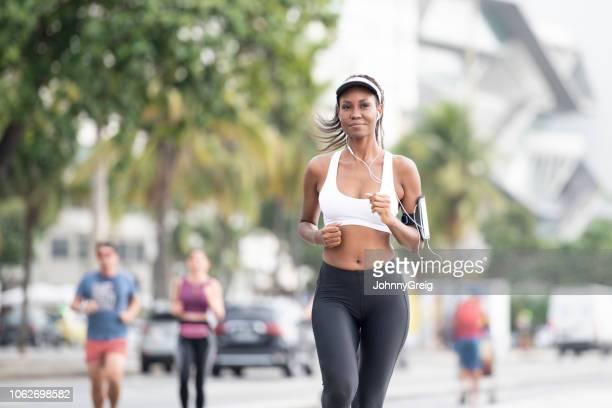 junge frau mit kopfhörern und schrittzähler auf arm laufen - strand von copacabana stock-fotos und bilder