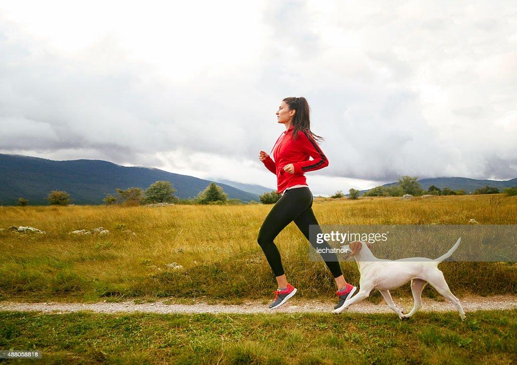 Giovane donna con il suo cane da jogging : Foto stock