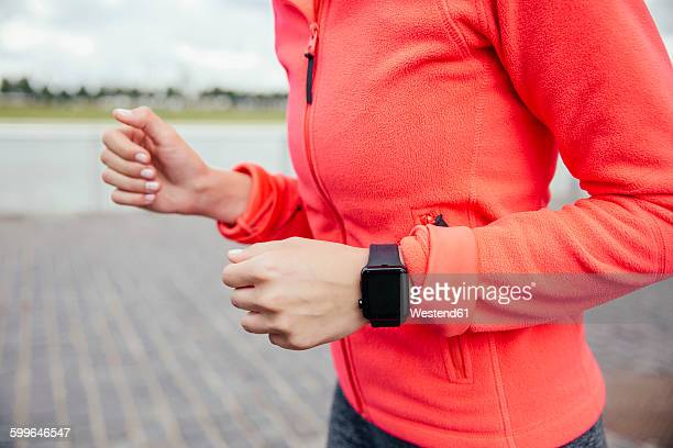 Young woman jogging with smart watch