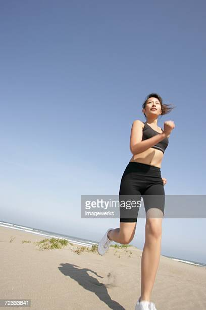 a young woman jogs along the beach on a bright sunny day - ブラトップ ストックフォトと画像