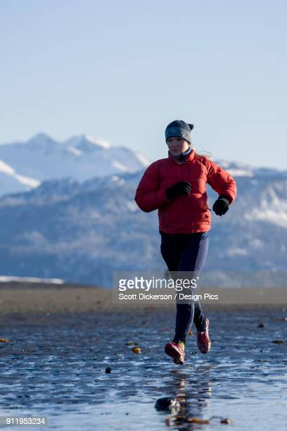 a young woman jogs along the wet beach in winter - home run ストックフォトと画像