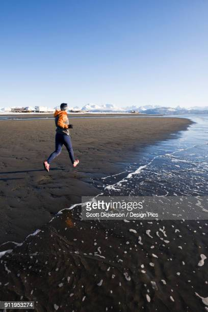 a young woman jogs on the wet beach at the waters edge - home run ストックフォトと画像