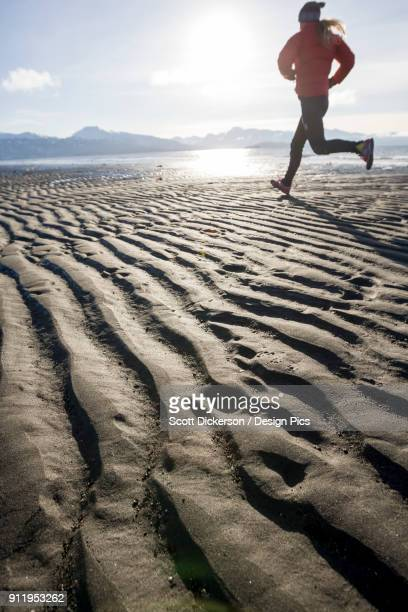 a young woman jogs on the wet beach - home run ストックフォトと画像